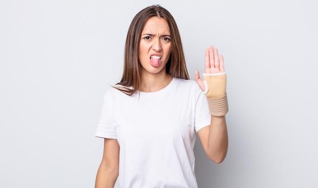 Młoda ładna kobieta czuje się zdegustowana i podrażniona i wymawia język. koncepcja bandaża ręcznego