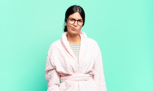 Młoda ładna kobieta czuje się zdezorientowana i wątpiąca, zastanawia się lub próbuje wybrać lub podjąć decyzję. koncepcja piżamy