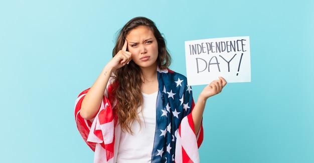 Młoda ładna kobieta czuje się zdezorientowana i zakłopotana, pokazując, że jesteś szaloną koncepcją dnia niepodległości