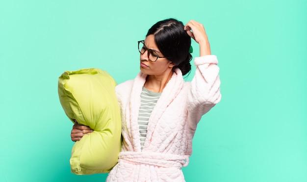 Młoda ładna kobieta czuje się zdezorientowana i zdezorientowana, drapiąc się po głowie i patrząc w bok. koncepcja piżamy