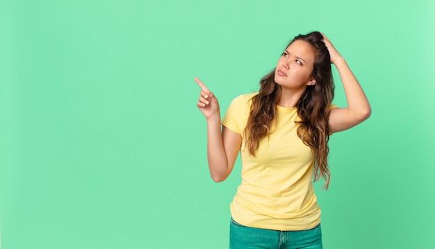 Młoda ładna kobieta czuje się zdezorientowana i zdezorientowana, drapiąc się po głowie i wskazując na miejsce na kopię