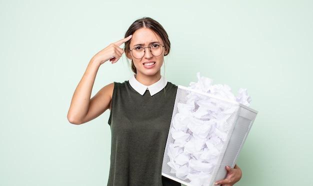 Młoda ładna kobieta czuje się zdezorientowana i zdezorientowana, pokazując, że jesteś szalony. koncepcja kosza z kulkami papierowymi