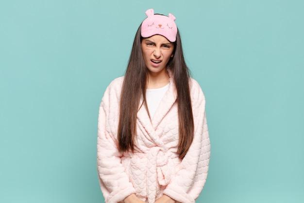 Młoda ładna kobieta czuje się zdezorientowana i zdezorientowana, z tępym, oszołomionym wyrazem twarzy, patrzącą na coś nieoczekiwanego. budząc koncepcję piżamy