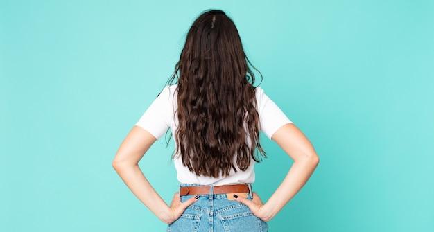 Młoda ładna kobieta czuje się zdezorientowana lub pełna lub ma wątpliwości i pytania, zastanawia się, z rękami na biodrach, widok z tyłu