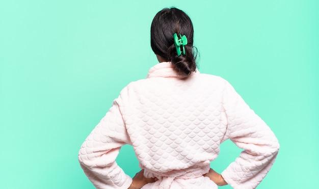 Młoda ładna kobieta czuje się zdezorientowana lub pełna lub wątpliwości i pytania, zastanawiając się, z rękami na biodrach, widok z tyłu. koncepcja piżamy