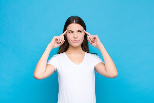 Młoda ładna kobieta czuje się zdezorientowana lub wątpiąca, koncentruje się na pomyśle, mocno myśli, chce skopiować przestrzeń na boku na niebieską ścianę
