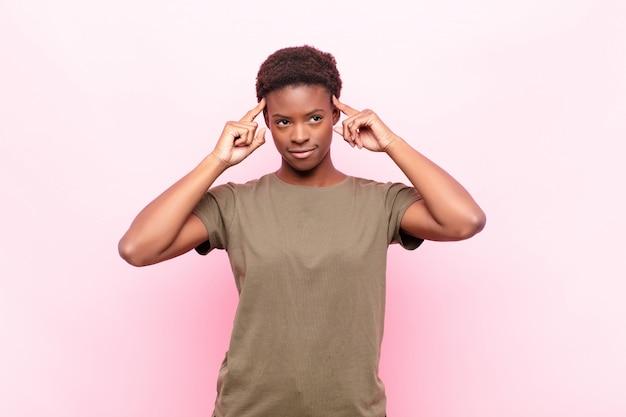 Młoda ładna kobieta czuje się zdezorientowana lub wątpiąca, koncentruje się na pomyśle, mocno myśli, chce skopiować przestrzeń na boku na różowej ścianie