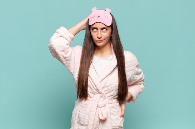 Młoda ładna kobieta czuje się zdziwiona i zdezorientowana, drapiąc się po głowie i patrząc w bok. budzi się w koncepcji piżamy
