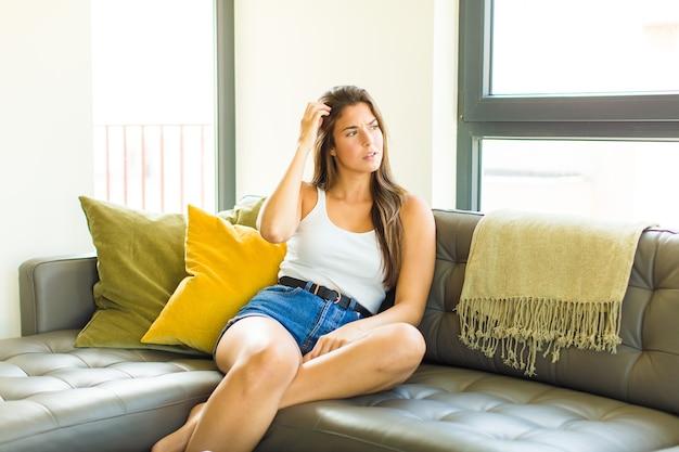 Młoda ładna kobieta czuje się zdziwiona i zdezorientowana, drapiąc się po głowie i patrząc w bok