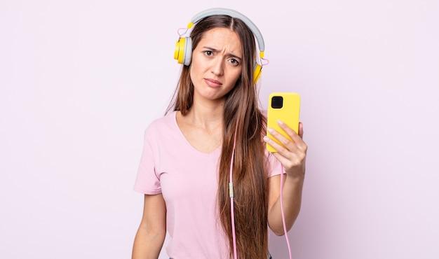 Młoda ładna kobieta czuje się zdziwiona i zdezorientowana. słuchawki i smartfon