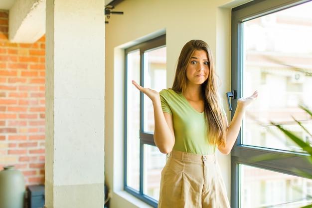 Młoda ładna kobieta czuje się zdziwiona i zdezorientowana, wątpi, rozważa lub wybiera różne opcje z zabawnym wyrazem twarzy