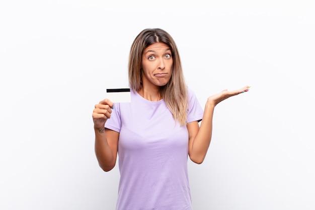Młoda ładna kobieta czuje się zdziwiona i zdezorientowana, wątpiąc, ważąc lub wybierając różne opcje z zabawnym wyrazem karty kredytowej