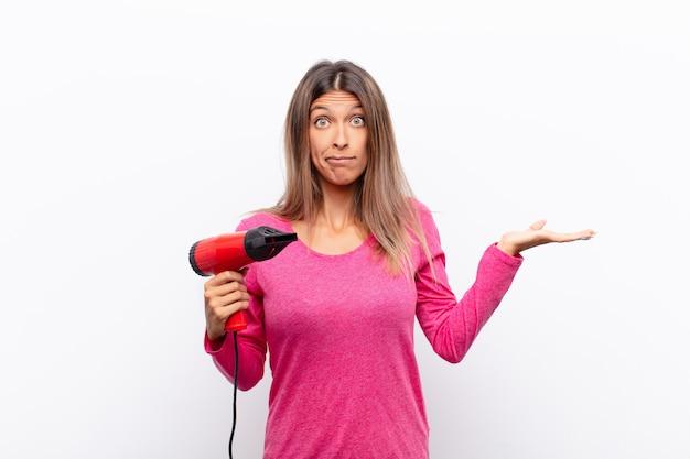 Młoda ładna kobieta czuje się zdziwiona i zdezorientowana, wątpiąc, ważąc lub wybierając różne opcje z zabawnym wyrazem twarzy za pomocą suszarki do włosów.