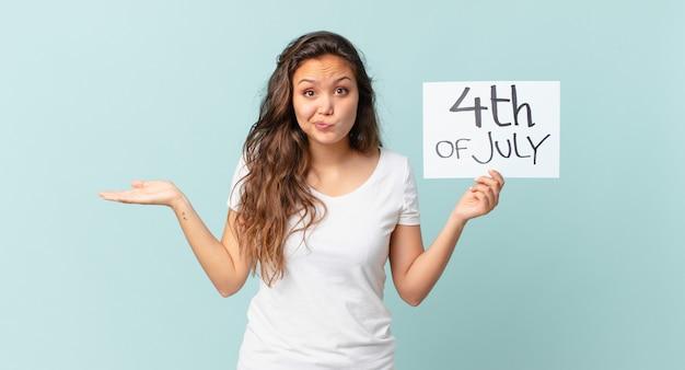 Młoda ładna kobieta czuje się zdziwiona, zdezorientowana i wątpi w koncepcję dnia niepodległości