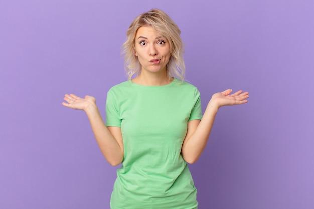 Młoda ładna kobieta czuje się zdziwiona, zdezorientowana i wątpi