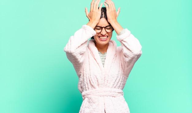 Młoda ładna kobieta czuje się zestresowana i niespokojna, przygnębiona i sfrustrowana bólem głowy, podnosząc obie ręce do głowy. koncepcja piżamy