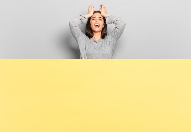 Młoda ładna kobieta czuje się zestresowana i niespokojna, przygnębiona i sfrustrowana bólem głowy, podnosząc obie ręce do głowy. skopiuj miejsce, aby umieścić swoją koncepcję