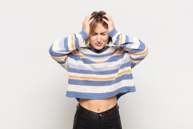 Młoda ładna kobieta czuje się zestresowana i sfrustrowana, podnosi ręce do głowy, czuje się zmęczona, nieszczęśliwa i ma migrenę