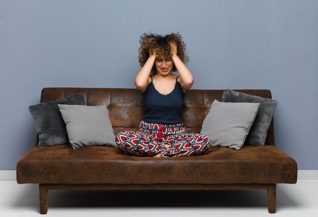 Młoda ładna kobieta czuje się zestresowana i sfrustrowana, podnosząc ręce do głowy, czując się zmęczona, nieszczęśliwa iz migreną siedzącą na kanapie.