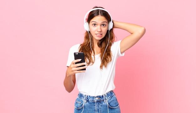 Młoda ładna kobieta czuje się zestresowana, niespokojna lub przestraszona, z rękami na głowie, słuchawkami i smartfonem