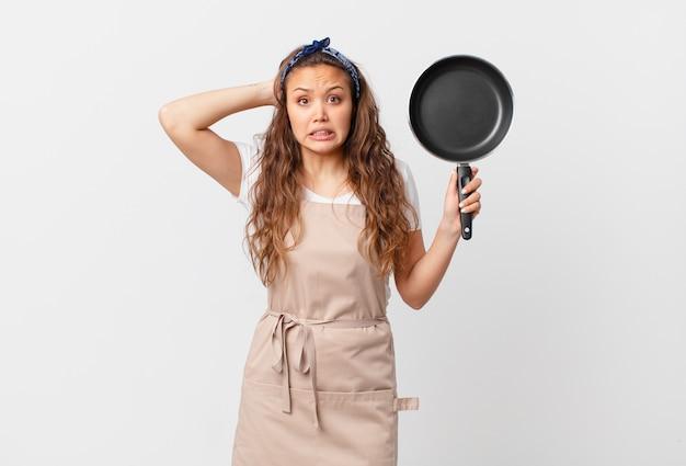 Młoda ładna kobieta czuje się zestresowana, niespokojna lub przestraszona, z rękami na koncepcji szefa kuchni i trzymająca patelnię