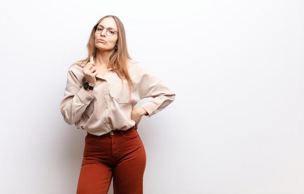 Młoda ładna kobieta czuje się zestresowana, niespokojna, zmęczona i sfrustrowana, ciągnie szyję koszuli, wygląda na sfrustrowaną problemem na białej ścianie