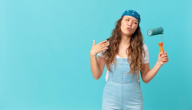 Młoda ładna kobieta czuje się zestresowana, niespokojna, zmęczona i sfrustrowana i maluje ścianę