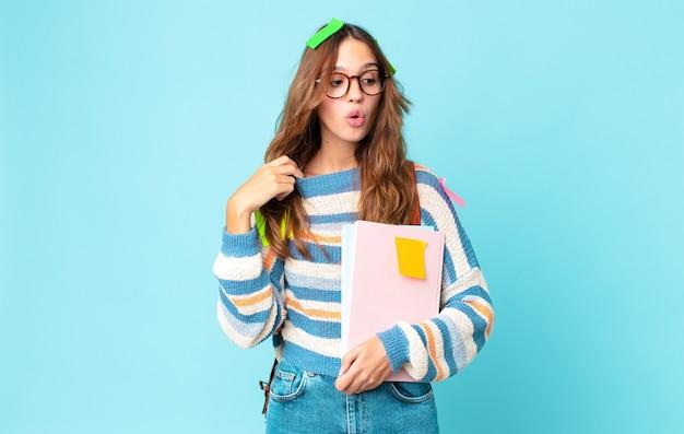 Młoda ładna kobieta czuje się zestresowana, niespokojna, zmęczona i sfrustrowana z torbą i trzymając książki