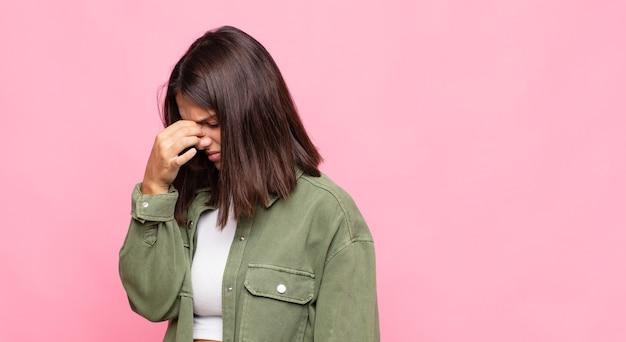 Młoda ładna kobieta czuje się zestresowana, nieszczęśliwa i sfrustrowana, dotyka czoła i cierpi na migrenę lub silny ból głowy