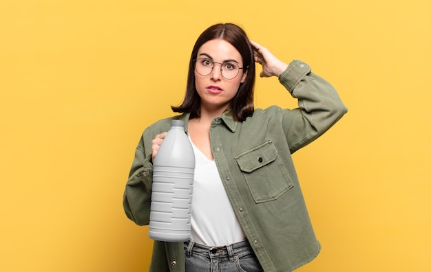Młoda ładna kobieta czuje się zestresowana, trzymając butelkę środka czyszczącego