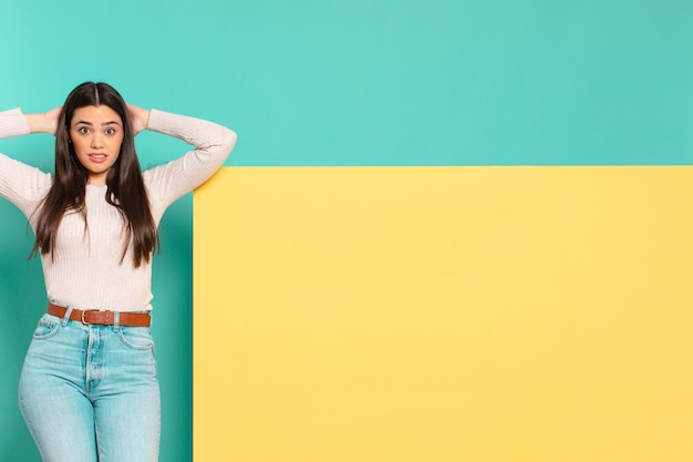Młoda ładna kobieta czuje się zestresowana, zmartwiona, niespokojna lub przestraszona, z rękami na głowie i panikuje w wyniku pomyłki. skopiuj miejsce, aby umieścić swoją koncepcję