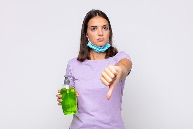 Młoda ładna kobieta czuje się zła, zła, zirytowana, rozczarowana lub niezadowolona, pokazując kciuki w dół z poważnym spojrzeniem
