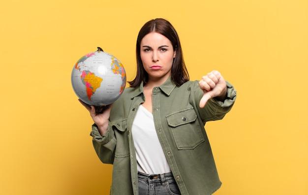 Młoda ładna kobieta czuje się zła, zła, zirytowana, rozczarowana lub niezadowolona, pokazuje kciuki w dół z poważnym spojrzeniem