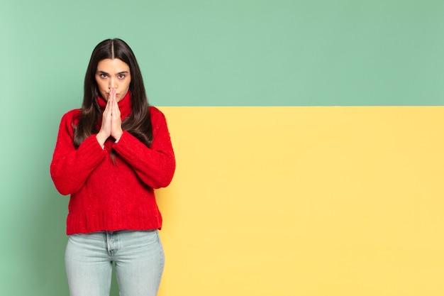Młoda ładna kobieta czuje się zmartwiona, pełna nadziei i religijna, modli się wiernie z zaciśniętymi dłońmi, błagając o przebaczenie. skopiuj miejsce, aby umieścić swoją koncepcję