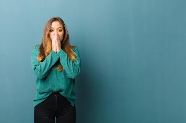 Młoda ładna kobieta czuje się zmartwiona, zdenerwowana i przestraszona, zakrywa usta dłońmi, wygląda na zaniepokojoną i popsuła