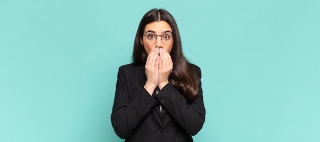 Młoda ładna kobieta czuje się zmartwiona, zdenerwowana i przestraszona, zakrywa usta rękami, wygląda na zaniepokojoną i pomieszała się. pomysł na biznes