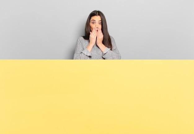 Młoda ładna kobieta czuje się zmartwiona, zdenerwowana i przestraszona, zakrywa usta rękami, wygląda na zaniepokojoną i pomieszała się. skopiuj miejsce, aby umieścić swoją koncepcję