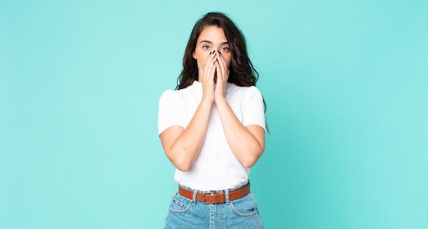 Młoda ładna kobieta czuje się zmartwiona, zdenerwowana i przestraszona, zakrywa usta rękami, wygląda na zaniepokojoną i pomieszała się