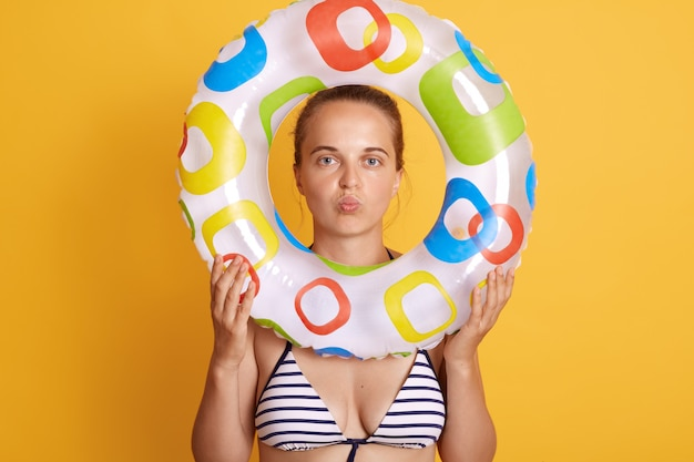 Młoda ładna kobieta czuje się zmęczona i sfrustrowana, wygląda na sfrustrowaną z powodu problemu, pozuje z wydymanymi ustami, trzyma nadmuchiwany pierścień przed twarzą, stoi przy żółtej ścianie.