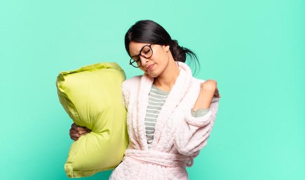 Młoda ładna kobieta czuje się zmęczona, zestresowana, niespokojna, sfrustrowana i przygnębiona, cierpi z powodu bólu pleców lub karku. koncepcja piżamy
