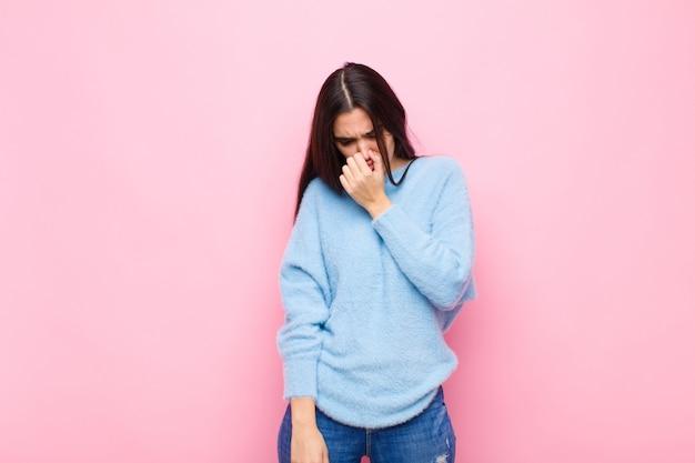 Młoda ładna kobieta czuje się zniesmaczona, trzymając nos, aby nie poczuć nieprzyjemnego i nieprzyjemnego smrodu na różowej ścianie