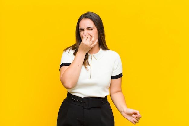 Młoda ładna kobieta czuje się zniesmaczona, trzymając nos, aby uniknąć wąchania nieprzyjemnego i nieprzyjemnego smrodu na pomarańczowej ścianie