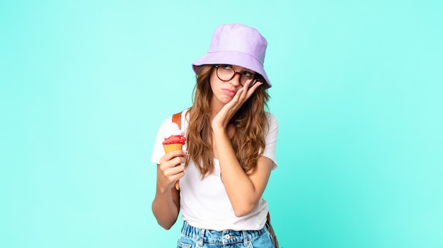 Młoda ładna kobieta czuje się znudzona, sfrustrowana i senna po męczącym trzymaniu lodów. koncepcja lato