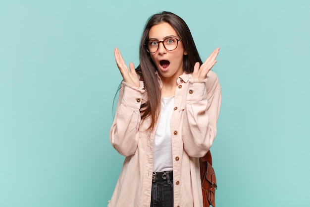 Młoda ładna kobieta czuje się zszokowana i podekscytowana, śmiejąc się, zdumiona i szczęśliwa z powodu nieoczekiwanej niespodzianki.