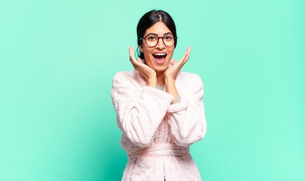 Młoda ładna kobieta czuje się zszokowana i podekscytowana, śmiejąca się, zdumiona i szczęśliwa z powodu niespodziewanej niespodzianki. koncepcja piżamy