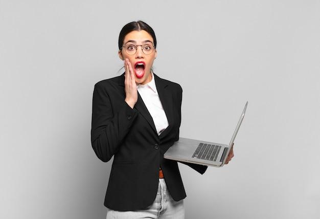 Młoda ładna kobieta czuje się zszokowana i przestraszona, wygląda na przerażoną z otwartymi ustami i dłońmi na policzkach. koncepcja laptopa