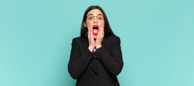 Młoda ładna kobieta czuje się zszokowana i przestraszona, wygląda na przerażoną z otwartymi ustami i rękami na policzkach. pomysł na biznes