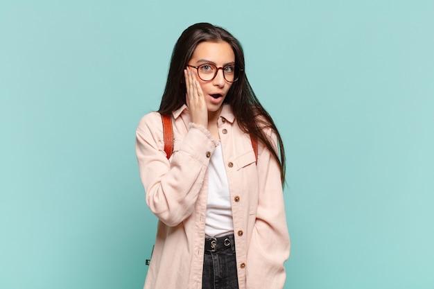 Młoda ładna kobieta czuje się zszokowana i zdumiona, trzymając twarzą w rękę z niedowierzaniem z szeroko otwartymi ustami. koncepcja studenta