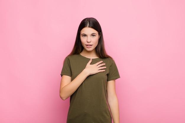 Młoda ładna kobieta czuje się zszokowana i zdziwiona, uśmiecha się, bierze dłoń do serca, jest szczęśliwa lub okazuje wdzięczność różowej ścianie