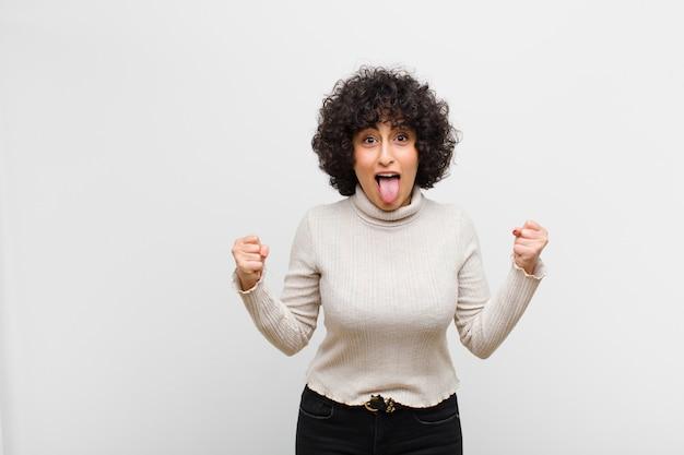 Młoda ładna kobieta czuje się zszokowana, podekscytowana i szczęśliwa, śmiejąc się i świętując sukces, mówiąc: wow!